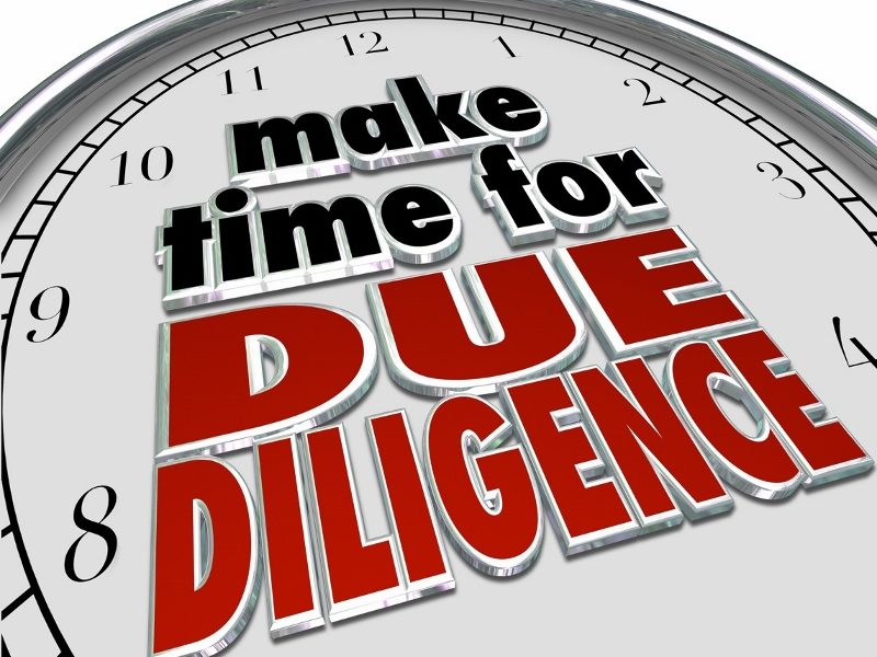 """A clock with the phrase, """"Make time for due diligence,"""" written on it in black and red letters."""