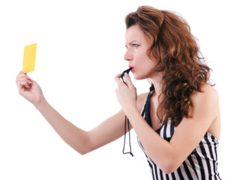 A female referee holds up a yellow card while blowing on a black whistle.