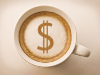 A latte in a coffee much with a dollar sign styled into the latte foam.